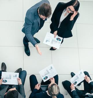 Draufsicht. projektmanager, der bei einem treffen mit der arbeitsgruppe fragen stellt. unternehmenskonzept.