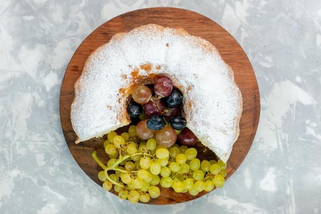Draufsicht pulverisierter kuchen köstlicher gebackener kuchen mit frischen trauben auf weißer oberfläche