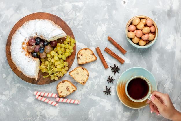 Draufsicht pulverisierter kuchen köstlicher gebackener kuchen mit frischen trauben und tasse tee auf weißem schreibtisch