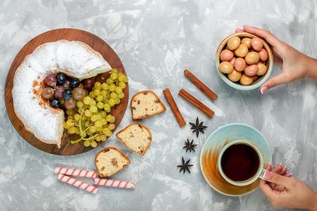 Draufsicht pulverisierter kuchen köstlicher gebackener kuchen mit frischen trauben und tasse tee auf weißer oberfläche