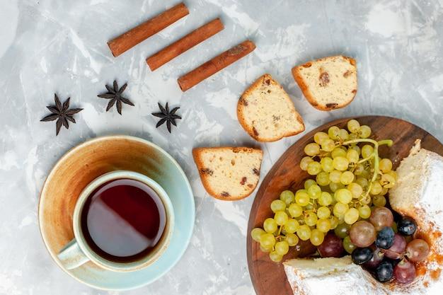 Draufsicht pulverisierter kuchen köstlicher gebackener kuchen mit frischen trauben und tee auf hellweißer oberfläche