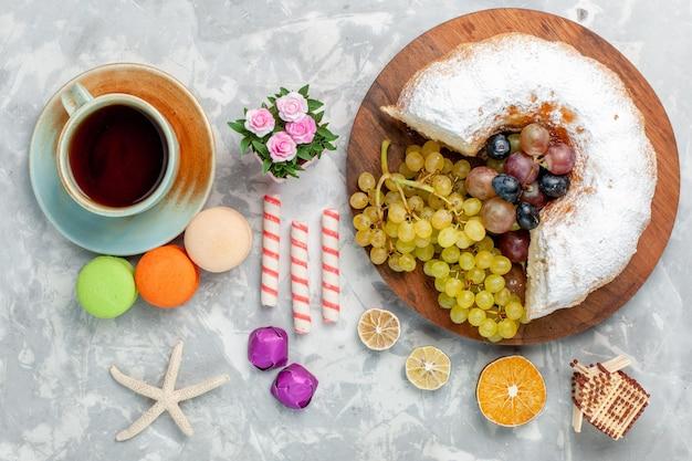 Draufsicht pulverisierter kuchen mit frischem traubentee und französischen macarons auf weißem schreibtisch