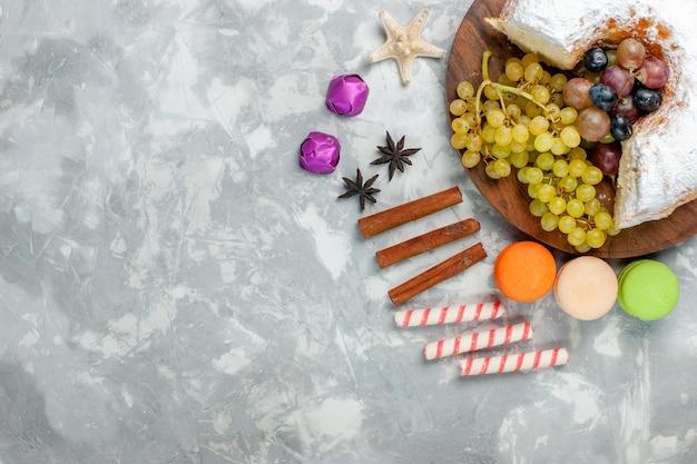 Draufsicht pulverisierter kuchen mit trauben-zimt und macarons auf der weißen oberfläche
