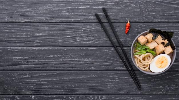 Draufsicht ramen gesunde suppe mit ei und stäbchen