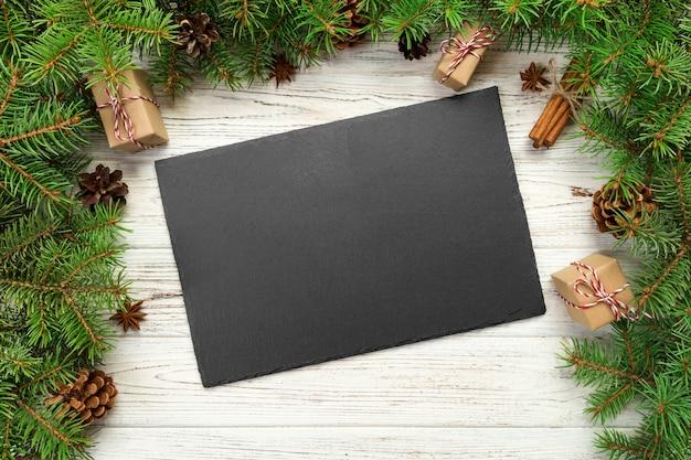 Draufsicht, rechteckige platte des leeren schwarzen schiefers auf hölzernem weihnachten, feiertagsabendessentellerkonzept mit dekor des neuen jahres
