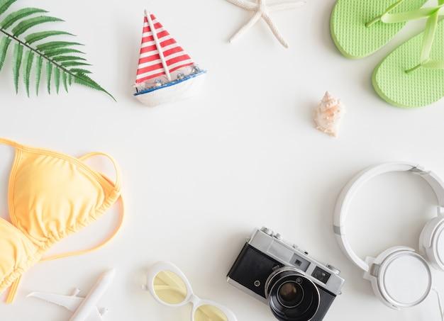 Draufsicht-reisekonzept mit bikini, gepäck und outfit des reisenden auf weißem hölzernem hintergrund, touristische grundlagen, vintage-toneffekt