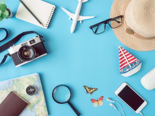 Draufsicht-reisekonzept mit retro-kamerafilmen, smartphone, karte, reisepass und outfit des reisenden auf blauem hintergrund mit kopierraum, touristischen grundlagen, vintage-toneffekt