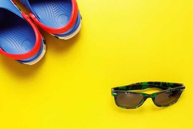 Draufsicht-reisekonzept mit schiefer, meereslebewesen, sonnenbrille auf gelbem hintergrund mit kopienraum für text