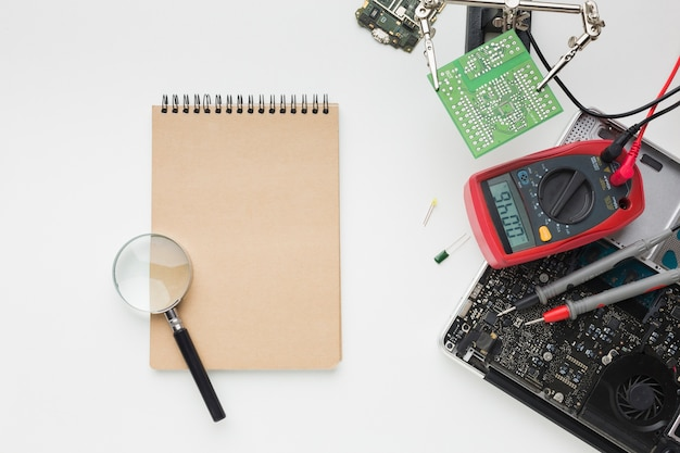 Draufsicht reparatur eines laptops mit notizblock