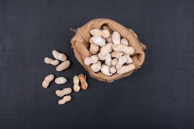 Draufsicht rohe erdnüsse im sack auf schwarz