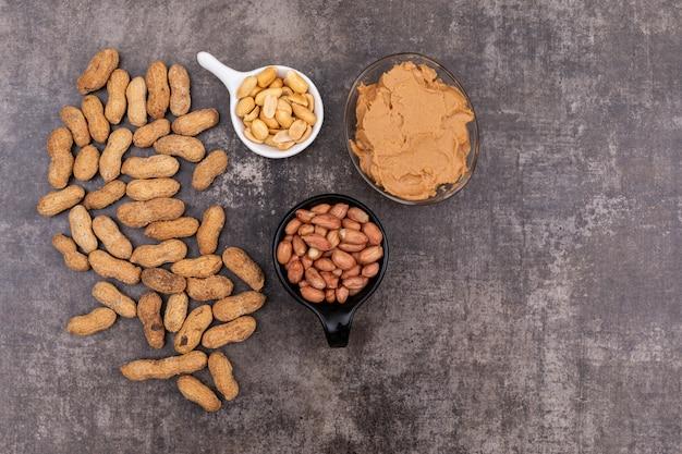 Draufsicht rohe erdnüsse in schüssel und erdnussbutter auf stein horizontal