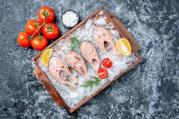 Draufsicht rohe fischscheiben mit eis auf holzbrett tomaten meersalz auf tisch mit freiem platz