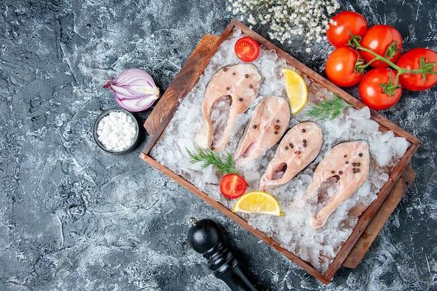 Draufsicht rohe fischscheiben mit eis auf holzbrett tomaten zwiebel meersalz auf tisch