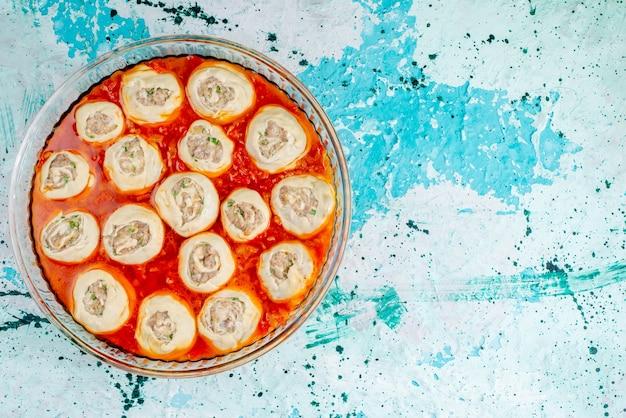 Draufsicht rohe fleischige teigteigscheiben mit hackfleisch innen mit tomatensauce innen glas