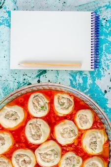 Draufsicht rohe fleischige teigteigscheiben mit hackfleisch innen mit tomatensauce innen glaspfanne mit notizblock auf dem blauen schreibtisch speiseteigfleisch abendessen