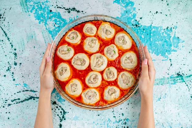 Draufsicht rohe fleischige teigteigscheiben mit hackfleisch mit tomatensauce in der glaspfanne, die in den ofen auf dem blauen schreibtisch essen mahlzeit teig teig fleisch abendessen geht