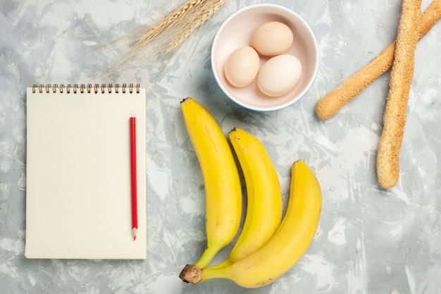 Draufsicht rohe ganze eier in kleinen teller mit brötchenbrot und bananen auf hellweißem schreibtisch rohkost mahlzeit frühstücksfruchtbrot