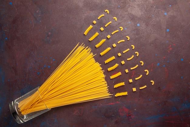 Draufsicht rohe italienische nudeln lange geformte gelbe farbe auf dem dunklen hintergrund nudeln italien teig mahlzeit rohe lebensmittelfarbe