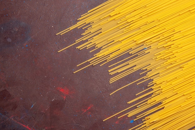 Draufsicht rohe italienische nudeln lange geformte gelbe farbe auf dunkler schreibtischnudeln italienischer teig mahlzeit lebensmittelfarbe