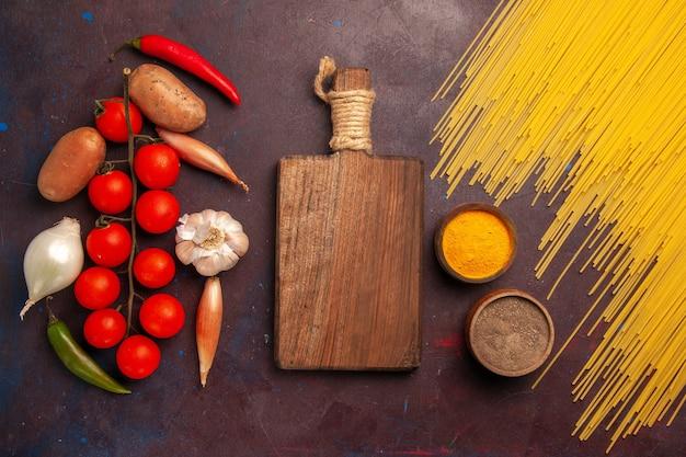 Draufsicht rohe italienische nudeln mit frischem gemüse auf dem dunklen hintergrund nudeln italien teig mahlzeit essen