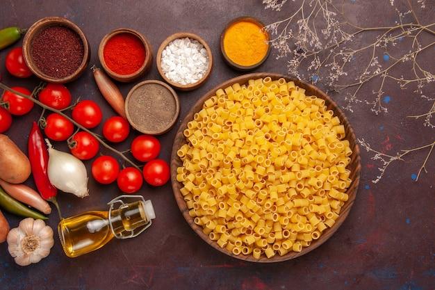 Draufsicht rohe italienische nudeln wenig geformte innenplatte auf dunklem schreibtisch nudelnahrungsmittel teig abendessen roh viele
