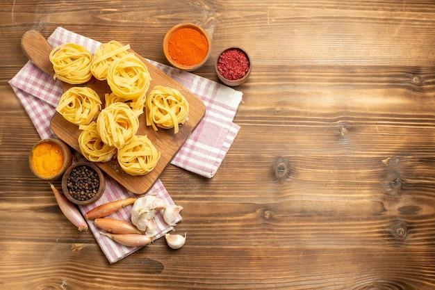 Draufsicht rohe nudeln gestaltete nudeln mit gewürzen auf braunem hölzernen hintergrundteigmahlzeitnahrungsmittelnudeln
