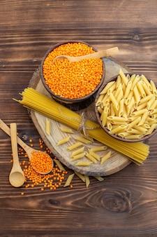 Draufsicht rohe nudeln mit orangefarbenen linsen auf brauner oberfläche