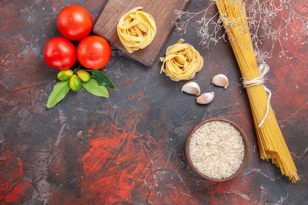 Draufsicht rohe nudeln mit reis und tomaten auf der dunklen oberfläche nudelteig roh