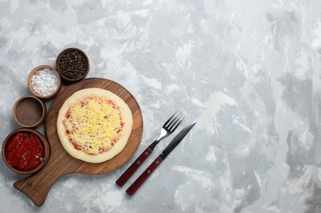 Draufsicht rohe pizza mit käse und gewürzen auf weißem schreibtisch