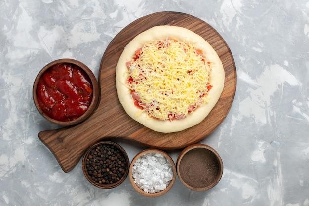 Draufsicht rohe pizza mit käse und verschiedenen gewürzen auf weiß