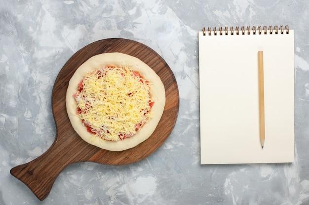 Draufsicht rohe pizza mit tomaten und käse auf weiß