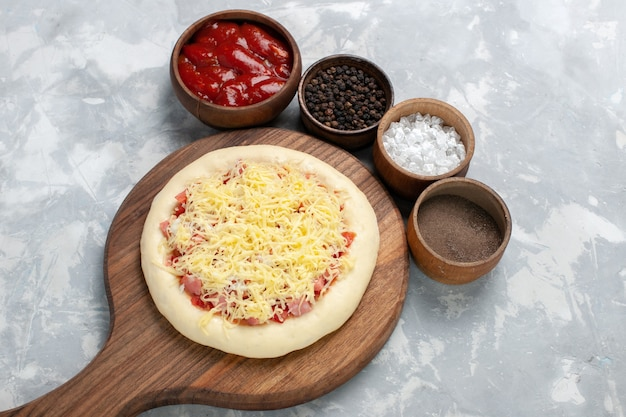 Draufsicht rohe pizza mit tomatensauce und käse auf weiß