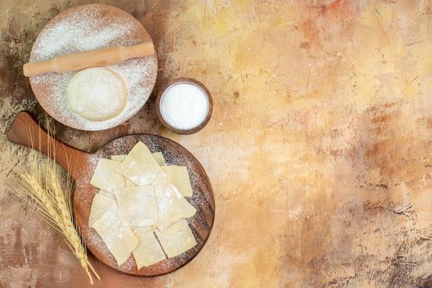 Draufsicht rohe teigscheiben mit mehl auf dem cremeschreibtisch