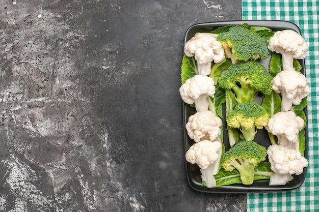 Draufsicht roher brokkoli und blumenkohl auf schwarzem rechteckigem teller auf grüner und weißer karierter serviette auf dunkler oberfläche mit kopierraum