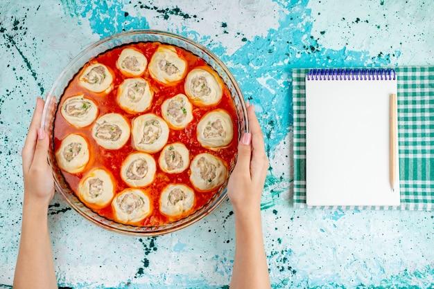 Draufsicht roher fleischiger teig teigscheiben mit hackfleisch mit tomatensauce in glaspfanne mit notizblock auf dem blauen schreibtisch essen mahlzeit teig fleisch
