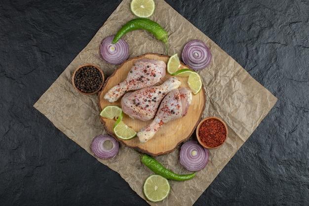 Draufsicht roher hühnertrommelstock und gemüse.
