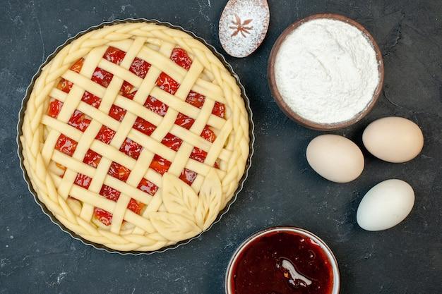 Draufsicht roher obstkuchen mit eiern und mehl auf dunklem hintergrund kuchen backen ofenfarbe süßer keksplätzchenzucker