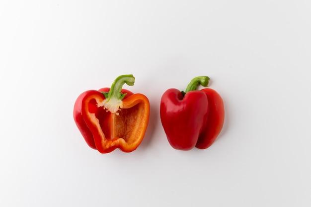 Draufsicht roher roter paprika halb geschnitten auf weißem tisch