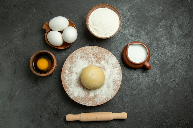 Draufsicht roher runder teig mit eiern und mehl auf grauem hintergrundnahrungsmittelteigmehl