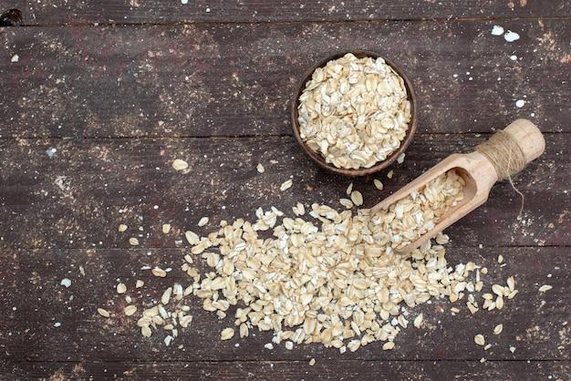 Draufsicht rohes haferflocken hell gefärbt auf braun, cracker snack brot trockenmahlzeit nützliche gesundheit frühstück