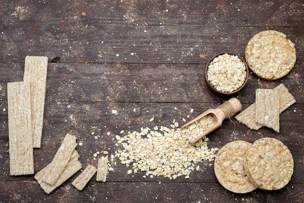 Draufsicht rohes haferflocken hell gefärbt mit chips und crackern auf braunem, crackersnackbrot-trockenmehl nützliches gesundheitsfrühstück