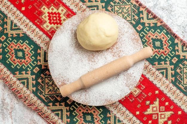 Draufsicht rohes teigstück mit mehl auf dem bunten teppich und weißem hintergrundmehl backen teig