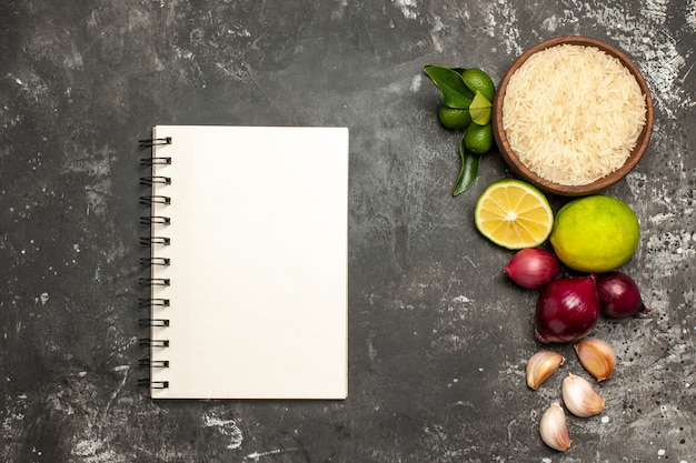 Draufsicht rohreis mit zwiebeln und knoblauch auf dunklem boden rohkost reifen salat