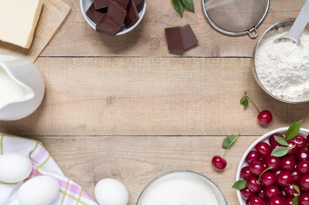 Draufsicht-rohzutaten zum kochen des kirschkuchens auf hölzernem hintergrund mit kopienraum