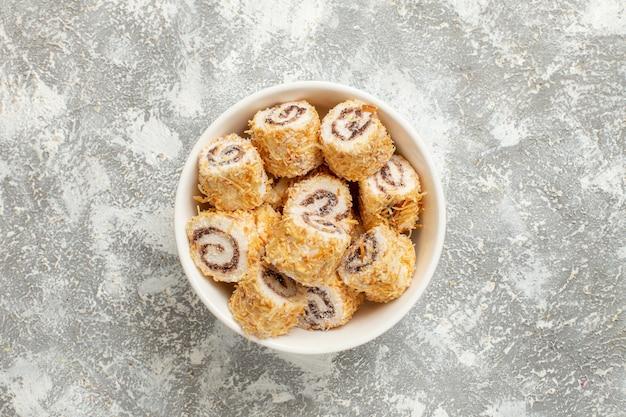 Draufsicht rollt süßigkeiten süße süßwaren innerhalb platte auf weißem hintergrund