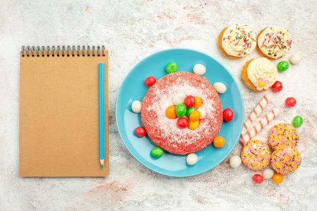 Draufsicht rosa kuchen mit bunten süßigkeiten und keksen auf weißer oberfläche goodie rainbow candy dessert farbkuchen