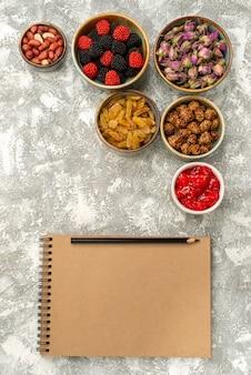 Draufsicht rosinen und nüsse mit confitures auf weißem hintergrund candy cake tea confiture biscuit