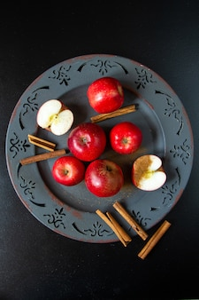 Draufsicht rote äpfel auf einem teller mit zimt