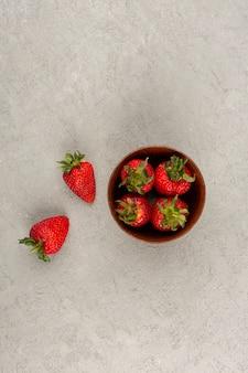 Draufsicht rote erdbeeren frisch reif weich innen und außen brauner topf auf dem hellen boden