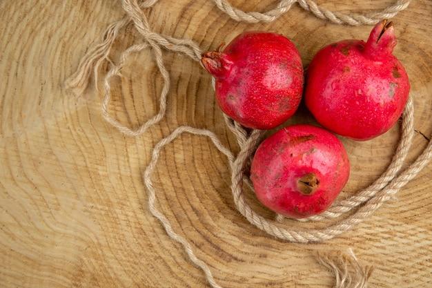 Draufsicht rote granatäpfel mit seilen auf holzschreibtisch